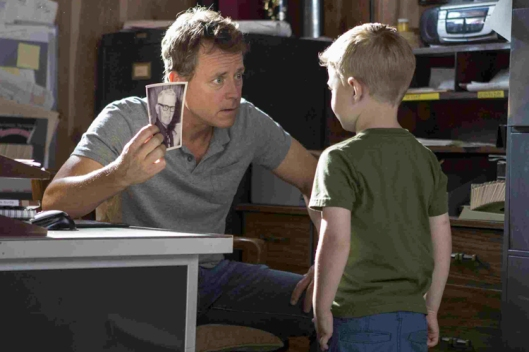 Todd (Greg Kinnear) shows Colton (Connor Corum) a picture of 'Pops' his grandfather in TriStar Pictures' HEAVEN IS FOR REAL.